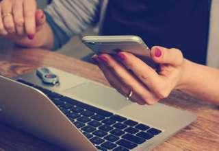 Laptop z wynajmu laptopa jest używany przez kobietę, która w ręku trzyma telefon.