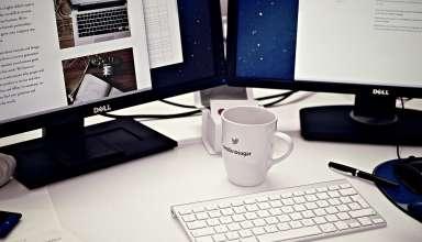 komputer z wypożyczalni komputerów; dwa monitory; klawiatura i kubek